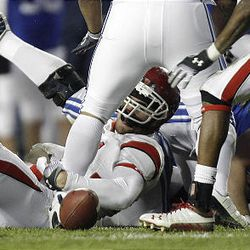 Utah defensive end Koa Misi tries to grab the ball after BYU running back Harvey Unga (45) lost the handle on it. The play was reviewed and the Cougars maintained control of the ball in the game at LaVell Edwards Stadium in Provo Saturday. BYU won in overtime 26-23.