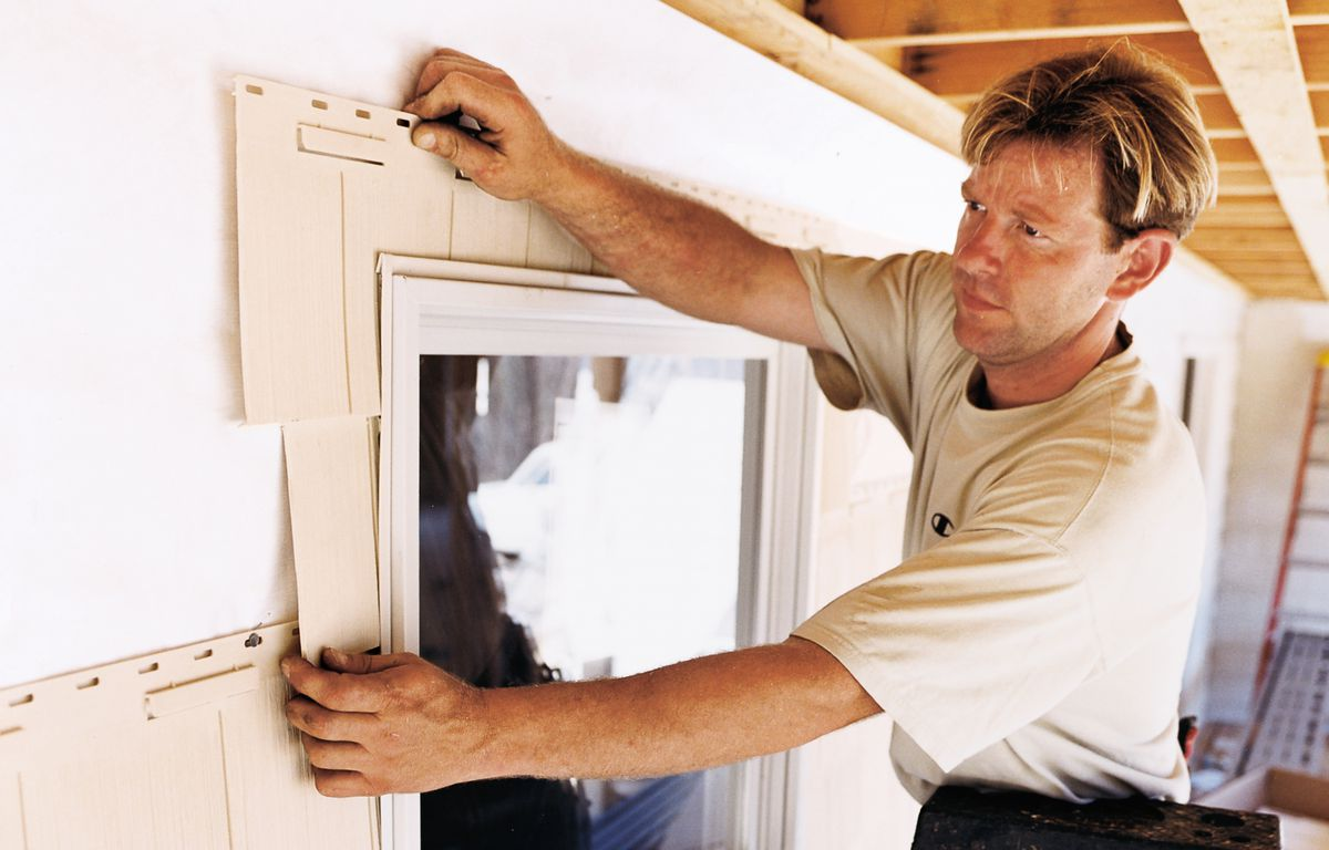 <p>Installer Joe Fagone slides a cut-to-fit, 4-foot-long panel of embossed-shingle siding around a window.</p>