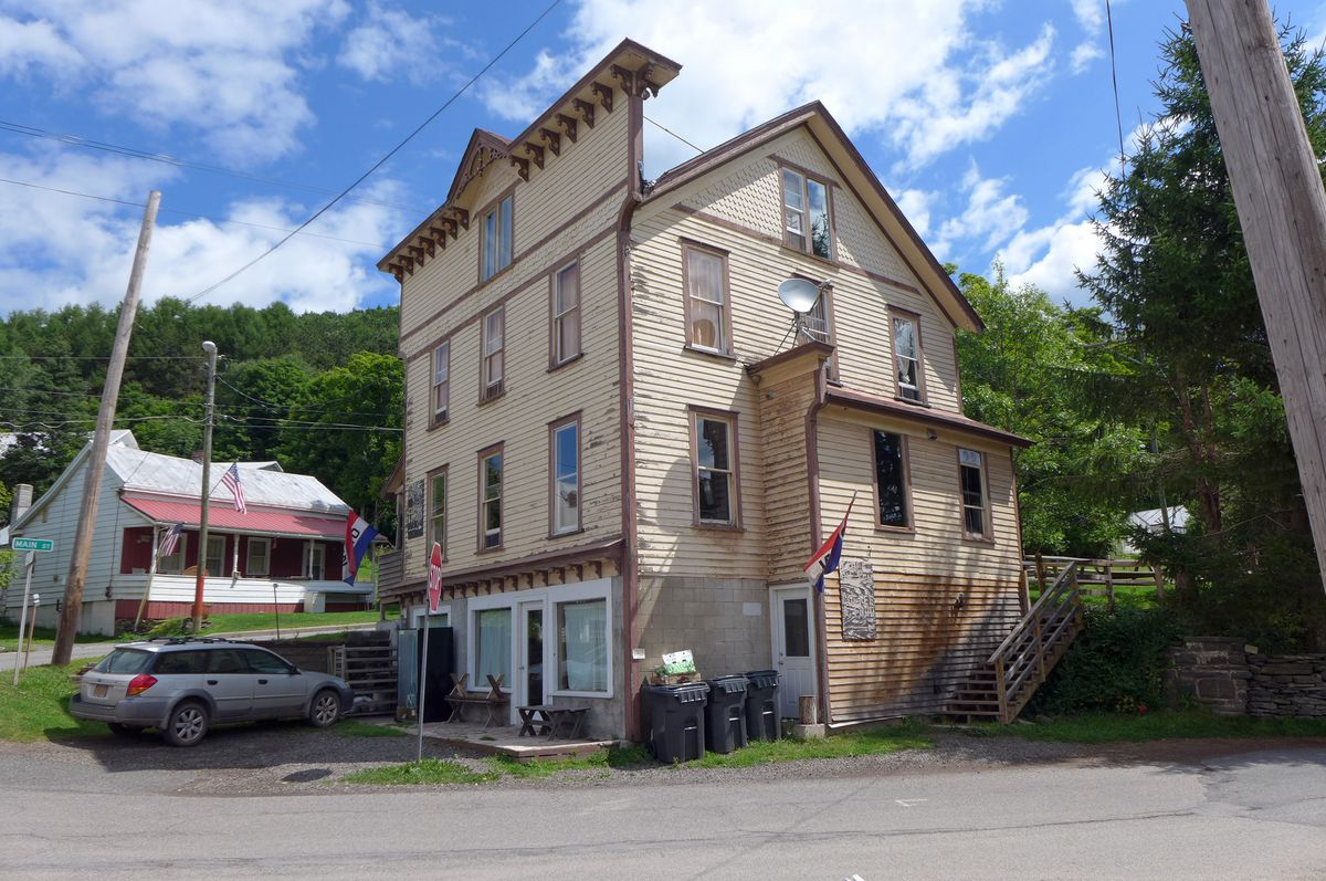 A four story house rising up, painted peeling beige, and in a state of some disrepair.