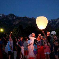People release flying lanterns during a vigil at Brookwood Elementary in Sandy for the victims of a shooting earlier that day, Tuesday, June 6, 2017.