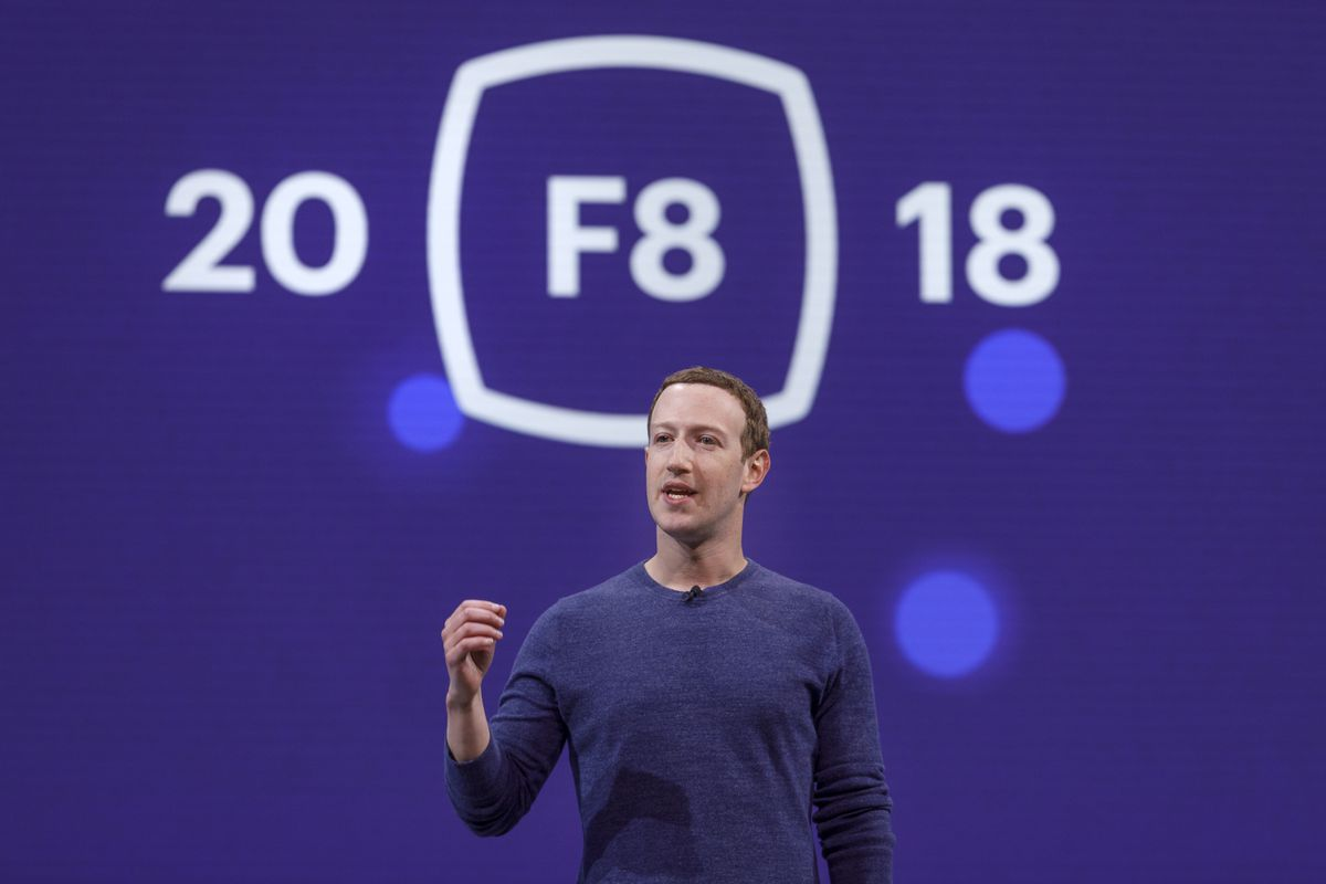 """Facebook CEO Mark Zuckerberg onstage in front of a backdrop that reads """"F8 2018"""""""