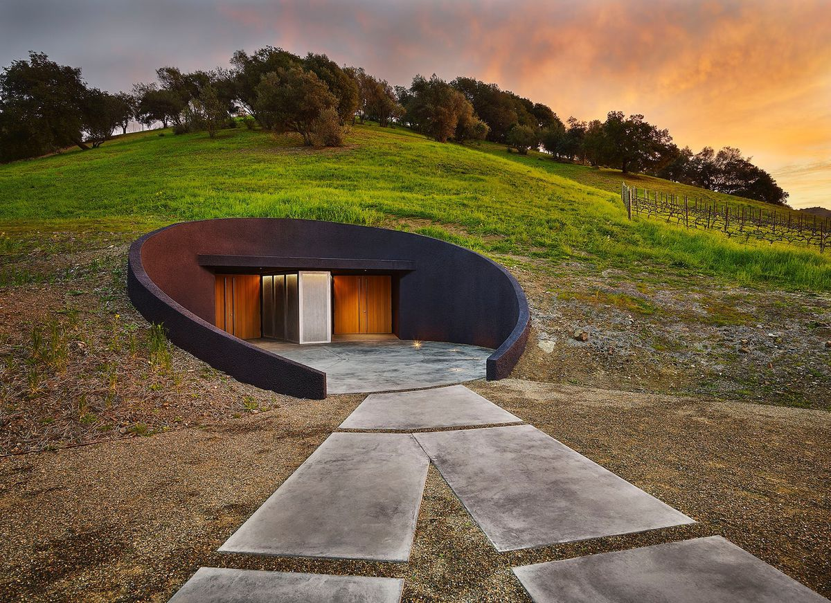 The exterior of the Odette Estate Winery in California. The winery is built into a hill and the roof is green grass. There are solar panels on the ground in the foreground.