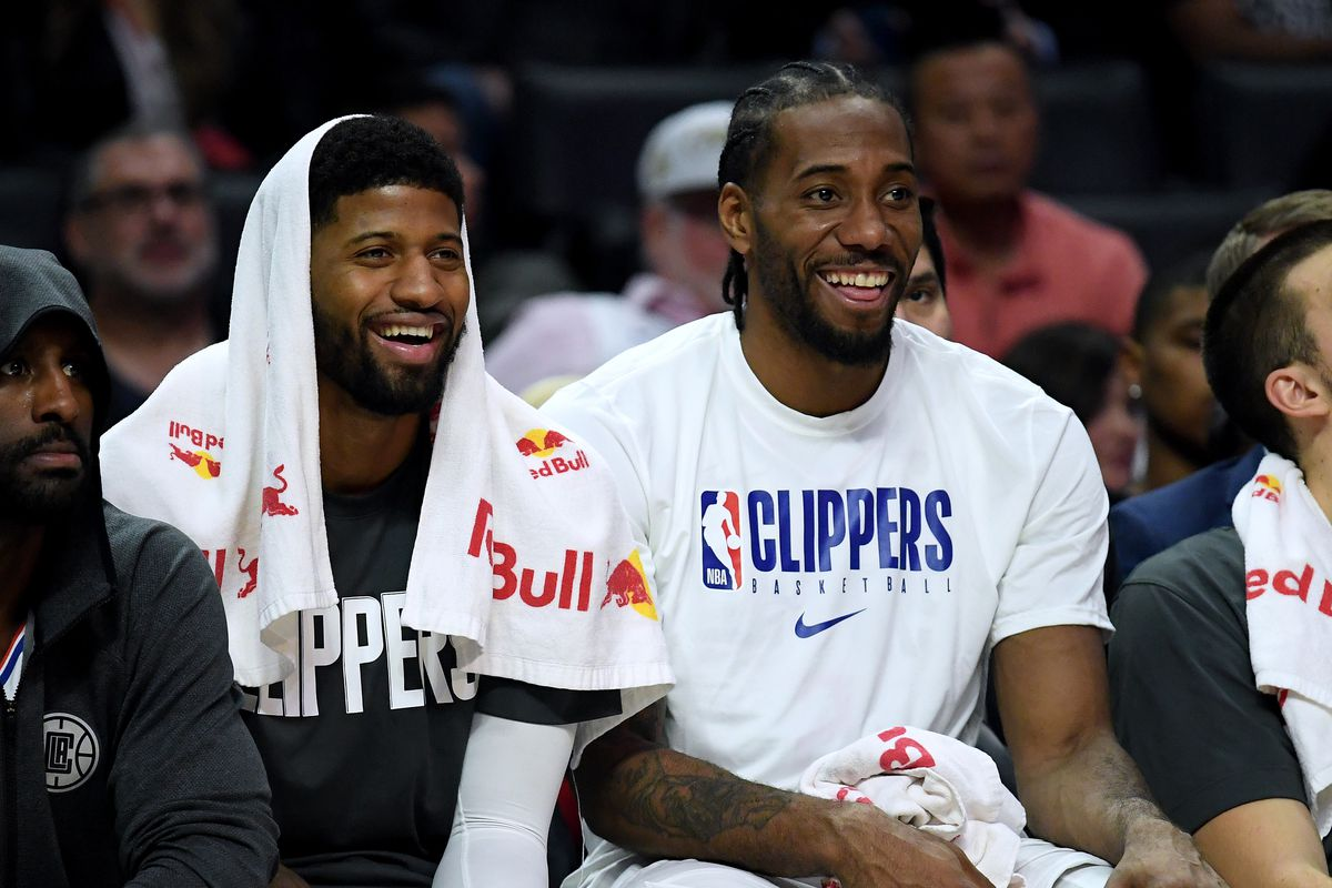 Paul George and Kawhi Leonard of the LA Clippers laugh on the bench during a 120-99 win over the Phoenix Suns at Staples Center on December 17, 2019 in Los Angeles, California.