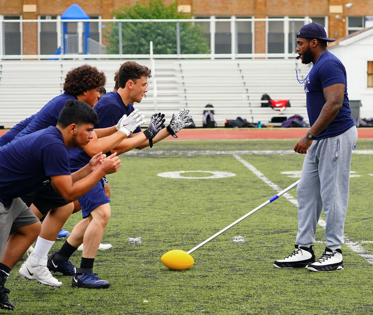 Chicago Academy coach Anthony Dotson runs a linemen drill at football practice.