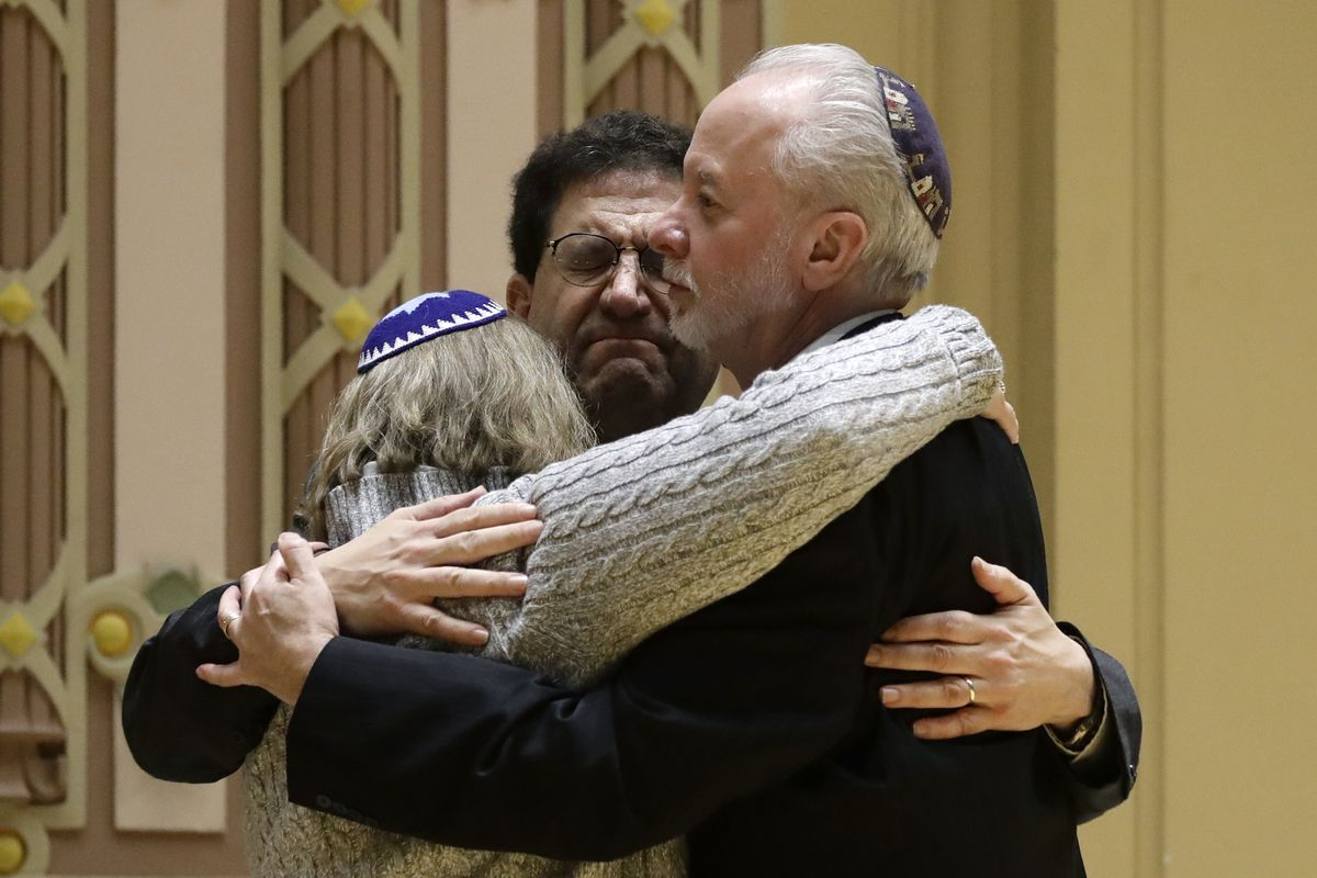 Rabbi Jeffrey Myers, right, hugs Rabbi Cheryl Klein, left, of Dor Hadash Congregation and Rabbi Jonathan Perlman during a community gathering held in the aftermath of a deadly shooting at the Tree of Life Synagogue in Pittsburgh, Sunday, Oct. 28.
