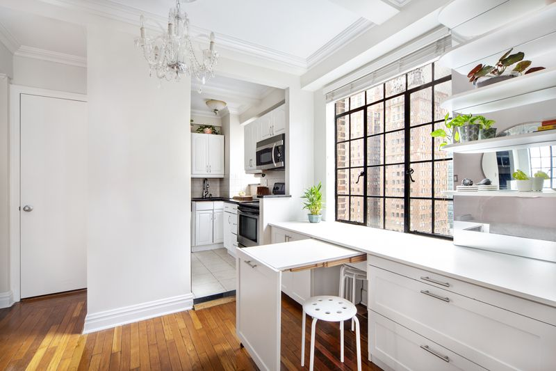 A small kitchen with white cabinets appears behind a pull-out built-in table.