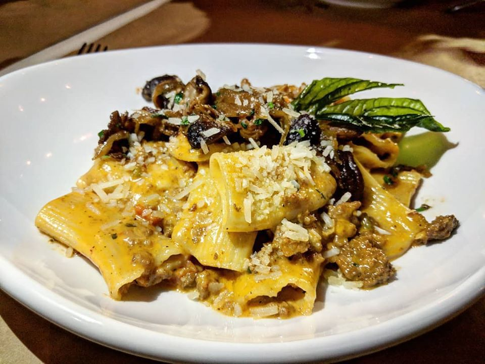 An Italian Bolognese dish, topped with cheese and fried basil, is on a white plate