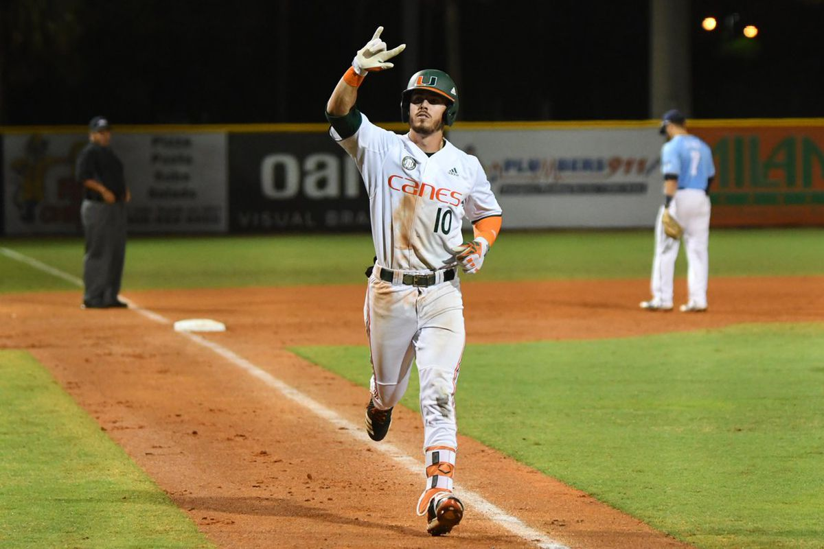 """Romy González, #10 in a Canes uniform, jogs home from third, making a """"let's rock"""" symbol with his hand"""