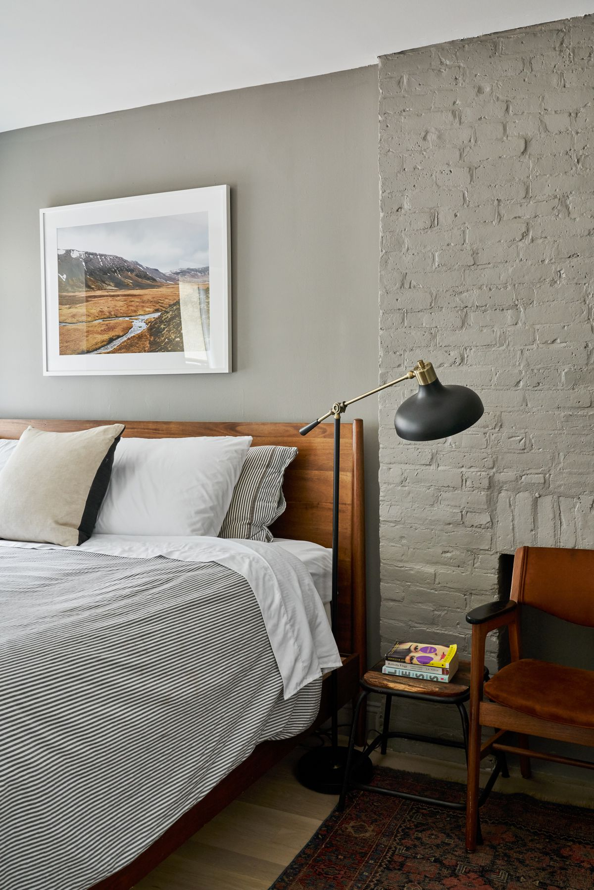 A bedroom with exposed brick and dark grey walls.