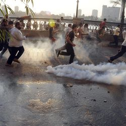 Egyptian protesters run from the site of clashes with security forces, unseen, near the U.S. embassy in Cairo, Egypt, Friday, Sept. 14, 2012, as part of widespread anger across the Muslim world about a film ridiculing Islam's Prophet Muhammad.