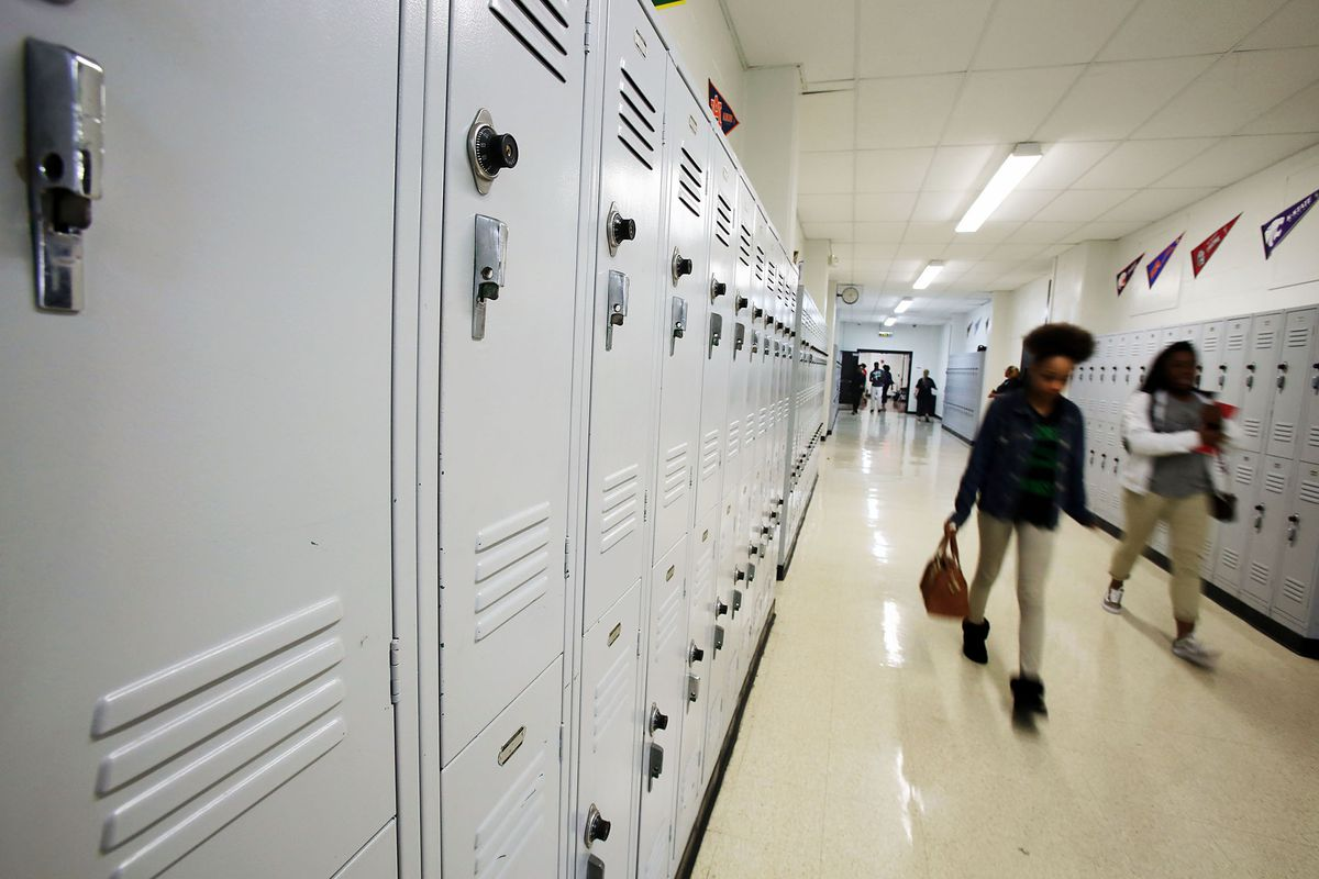 Students walk past lockers at Hillcrest High School, one of three Memphis high schools in the state-run Achievement School District.