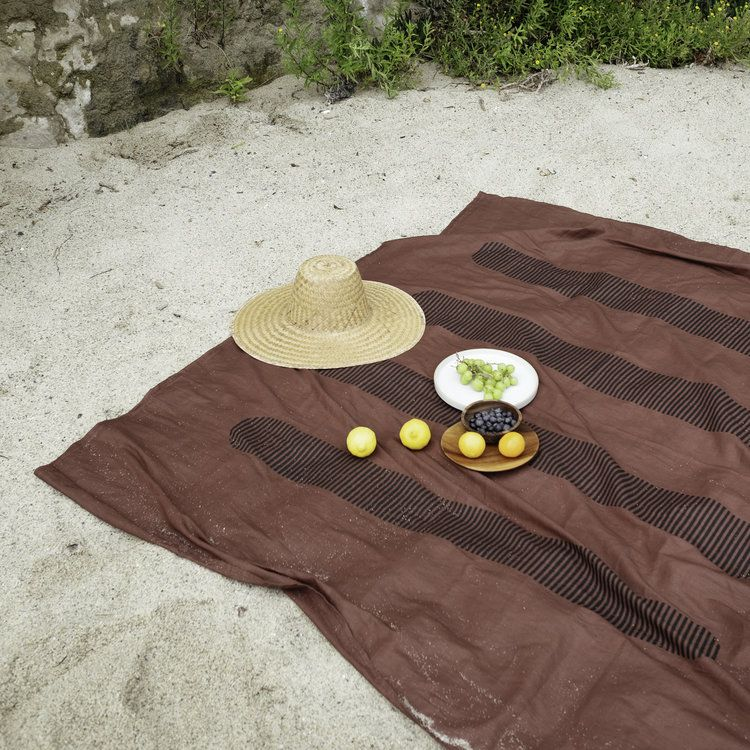 A linen blanket in a maroon red color is spread across the sand. A straw hat sits on top of the blanket.