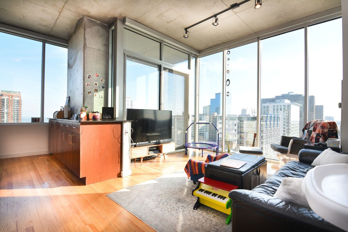 A loft with large windows, exposed concrete, and an open kitchen and living room.