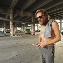 Christopher Paul, who is homeless, walks around where he lives under the freeway in Austin, Texas, on Tuesday, Oct. 20, 2020.