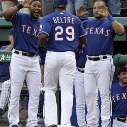 Texas Rangers' Elvis Andrus, left, and Yorvit Torrealba, right, congratulate teammate Adrian Beltre (29) on his solo home run off of New York Yankees' Phil Hughes in the second inning of a baseball game on Wednesday, April 25, 2012, in Arlington, Texas.