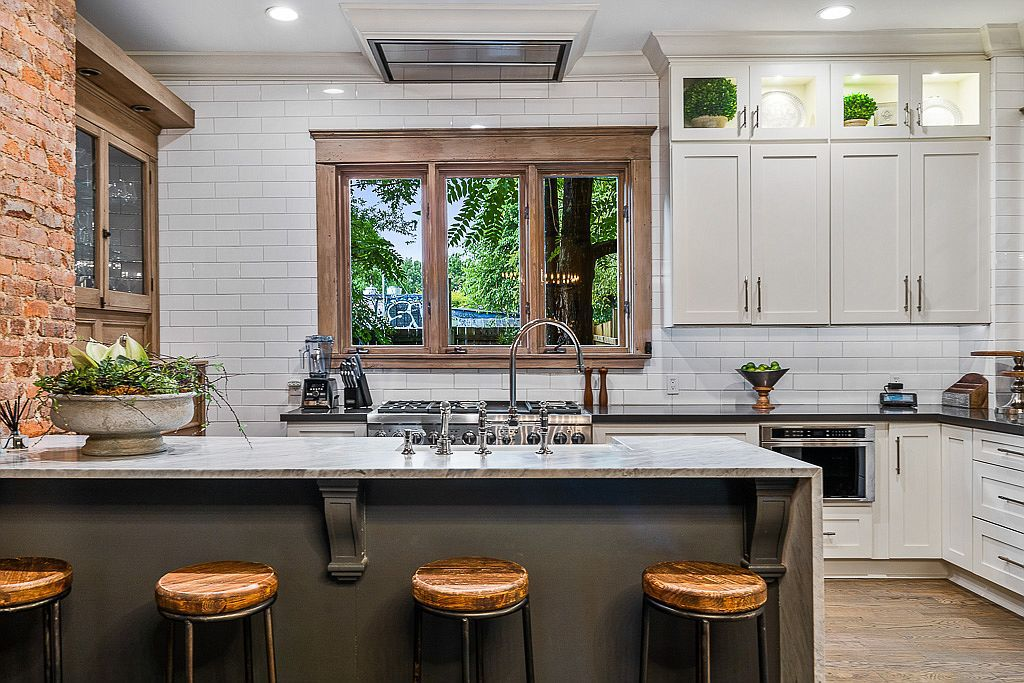 A renovated chef's kitchen with a brick wall and white tile.