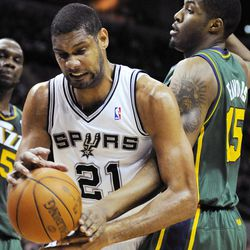 San Antonio Spurs' Tim Duncan (21) fights for a rebound with Utah Jazz's Derrick Favors during the first half of an NBA basketball game, Sunday, April 8, 2012, in San Antonio.