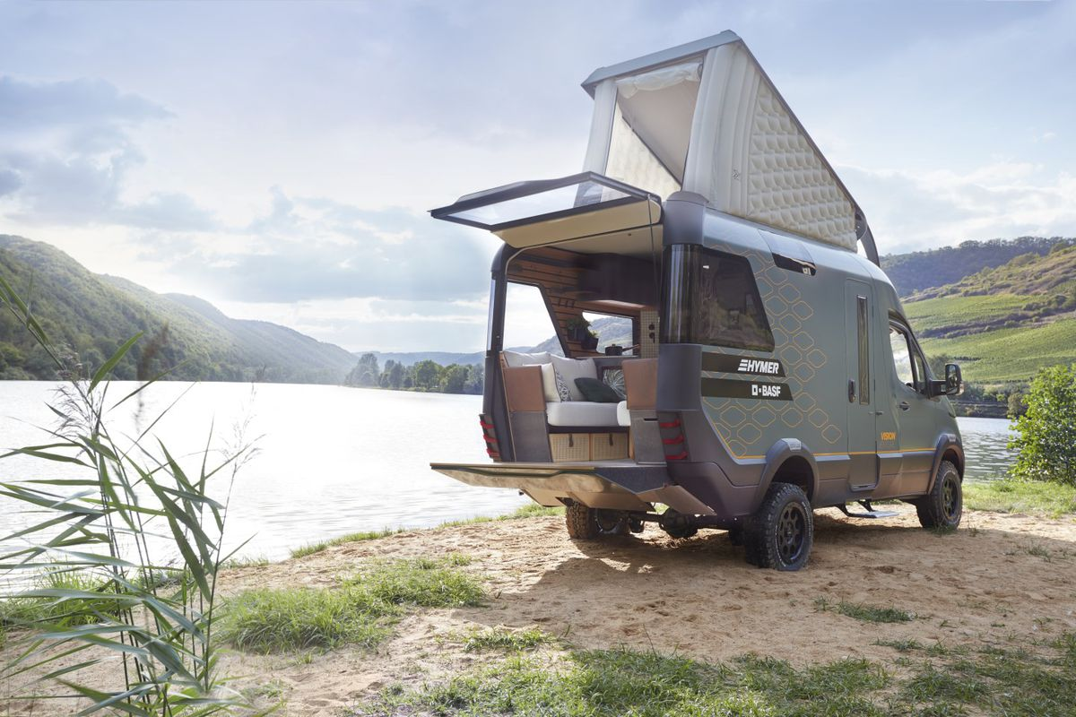 A rear view of the camper next to a lake. The camper's rooftop sleeping area is popped up, and you can see the rear tailgate open for entertaining.