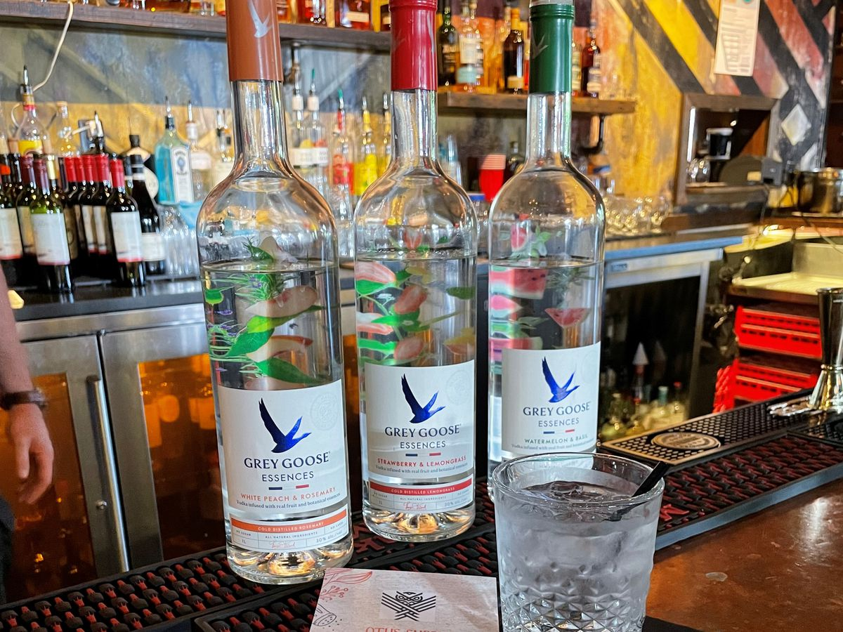 Three Grey Goose Essences liquor bottles on a bar with a clear drink in a low whiskey glass
