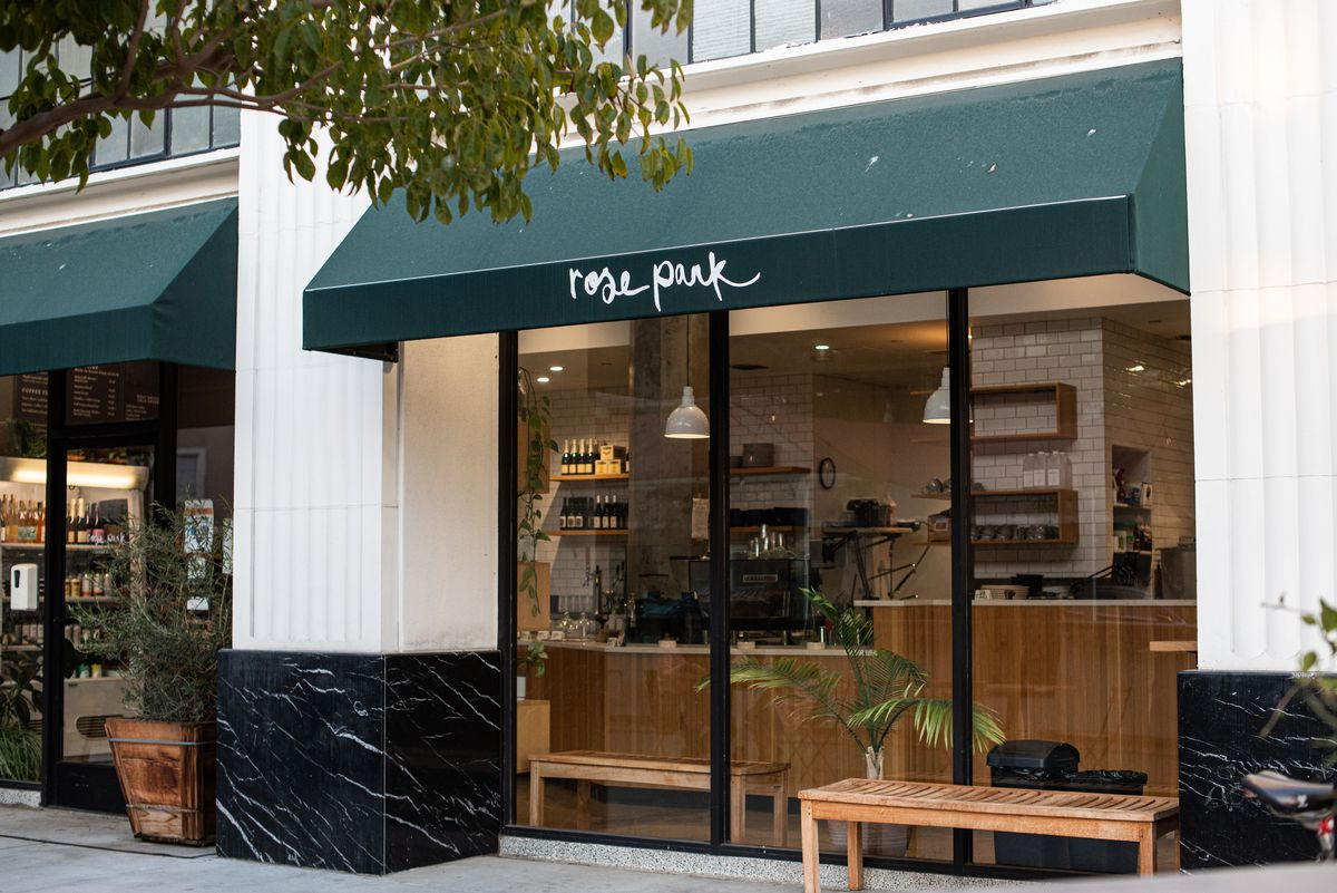 A dark green awning for a coffee shop named Rose Park.