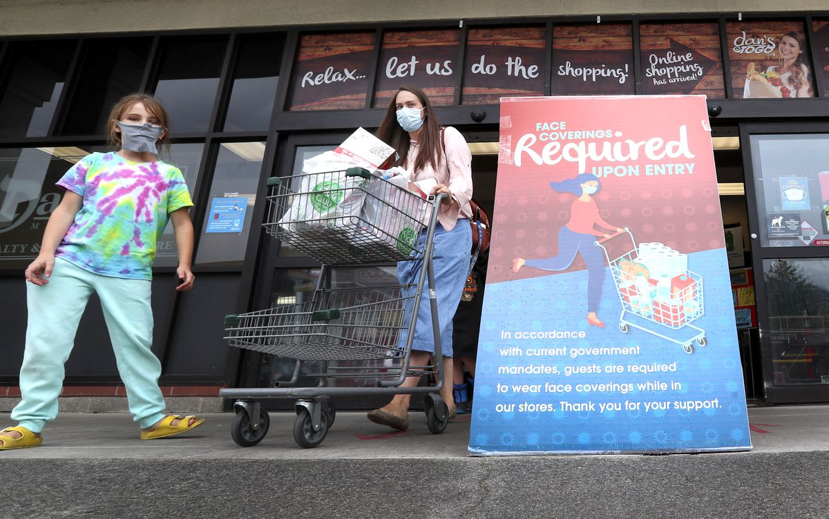 Emily Hone leaves Dan's Fresh Market at 1360 S. Foothill Blvd. in Salt Lake City, after shopping with her children Abigail, left, and John, not pictured, on Monday, June 29, 2020. New signs inform customers that face coverings are now required to enter the store.