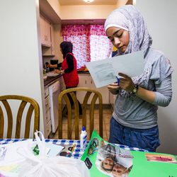 Nour Bilal, 15, does homework while her mother, Kholoud Abou Arida, prepares dinner at their home in Millcreek on Tuesday, Sept. 8, 2015.
