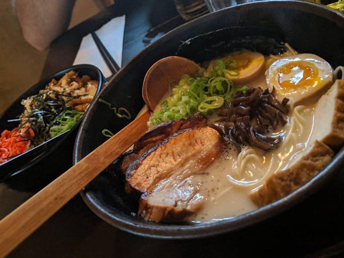 A wooden spoon in a bowl of ramen.