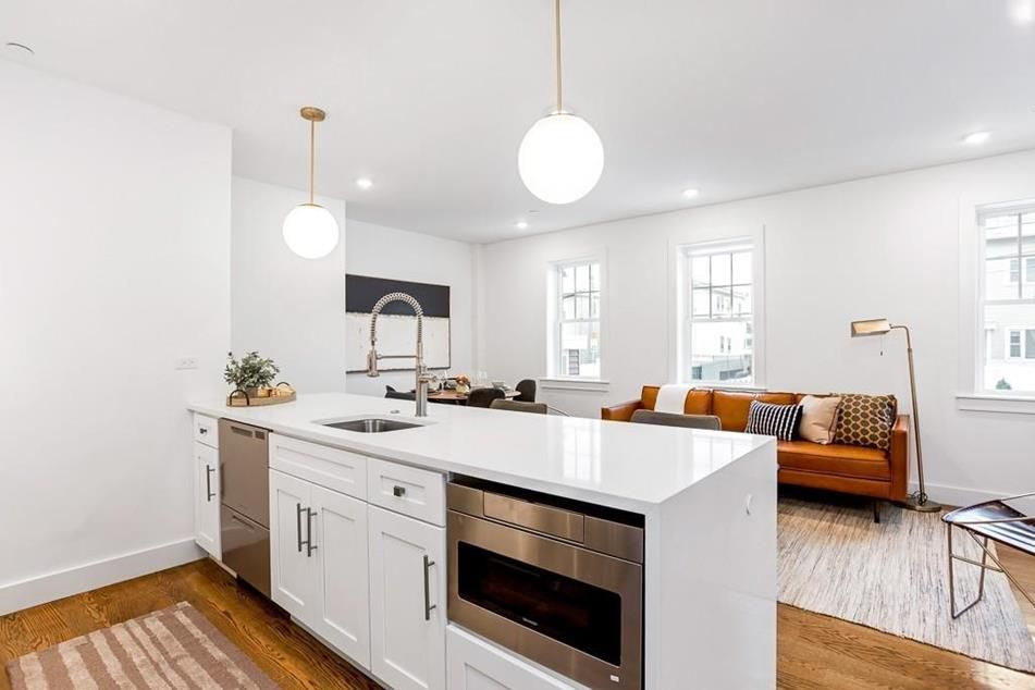 An open kitchen-living room area with a long granite counter separating them.