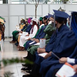 Students from Simon Youth Academy at Circle Centre Mall listen to Principal Robert Moses speak at their graduation Thursday.