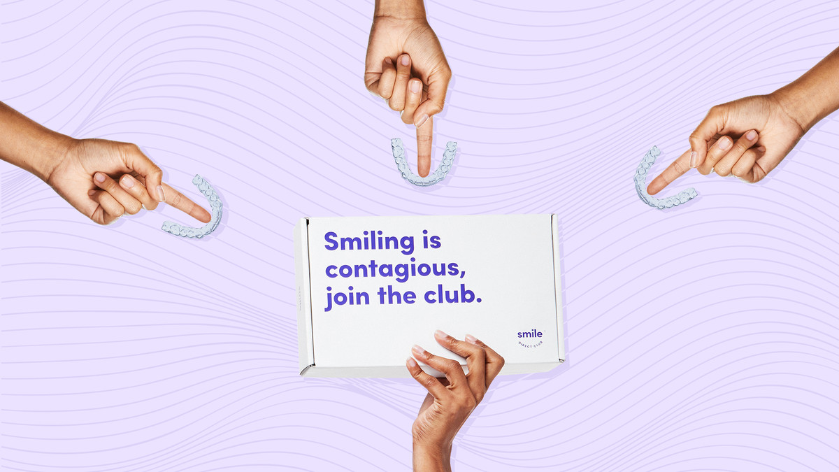 """Three hands hold up invisible aligners for your teeth from Smile Direct Club, and another hand holds up a purple box from Smile Direct Club that reads """"Smiling is contagious, join the club."""""""