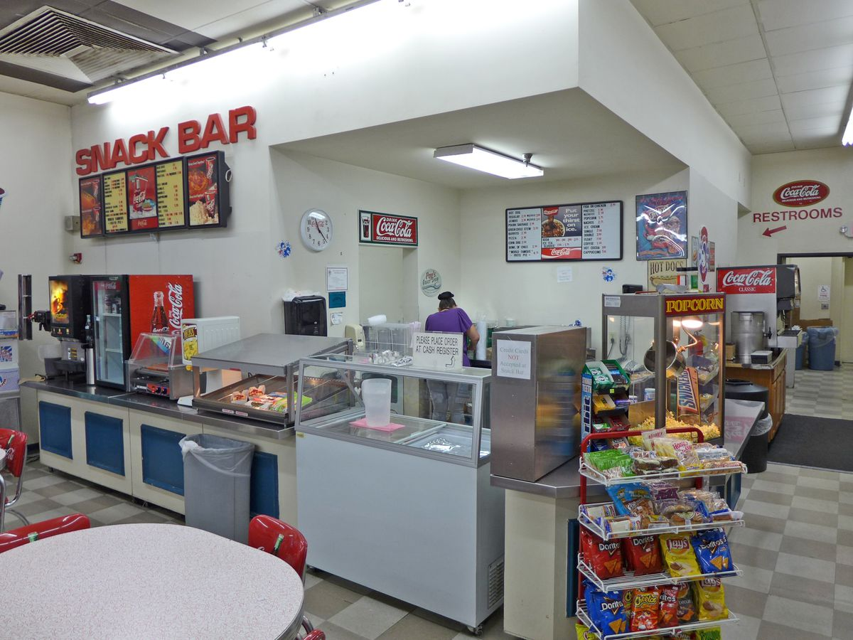 A white fast food kitchen with a couple of tables visible in the foreground.