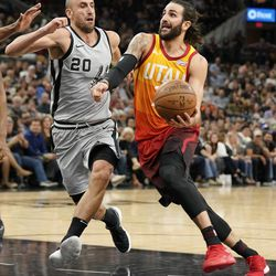 Utah Jazz's Ricky Rubio, right, drives against San Antonio Spurs' Manu Ginobili during the second half of an NBA basketball game Friday, March 23, 2018, in San Antonio. San Antonio won 124-120 in overtime. (AP Photo/Darren Abate)