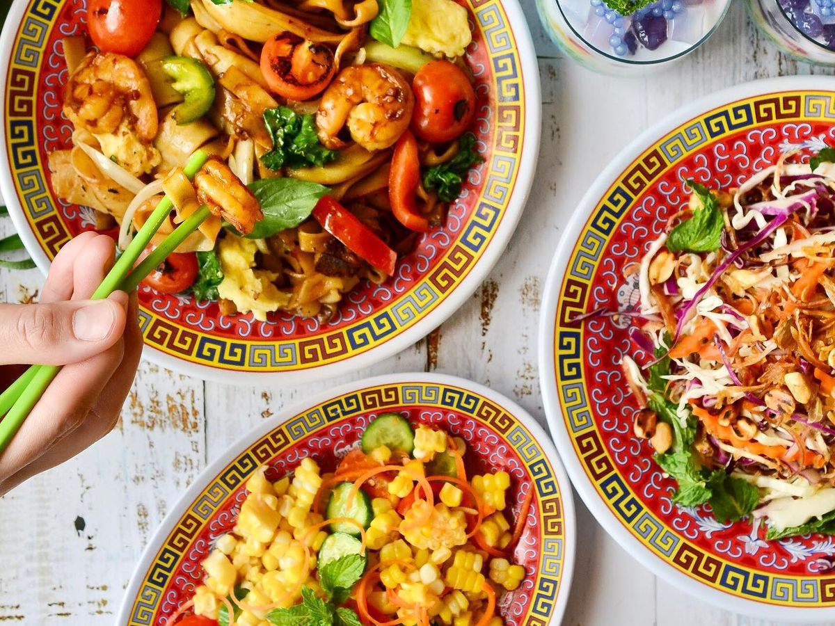 A table with several dishes, including a plate of stir-fried noodles that someone is eating with chopsticks, along with shaved banana blossom salad and corn salad