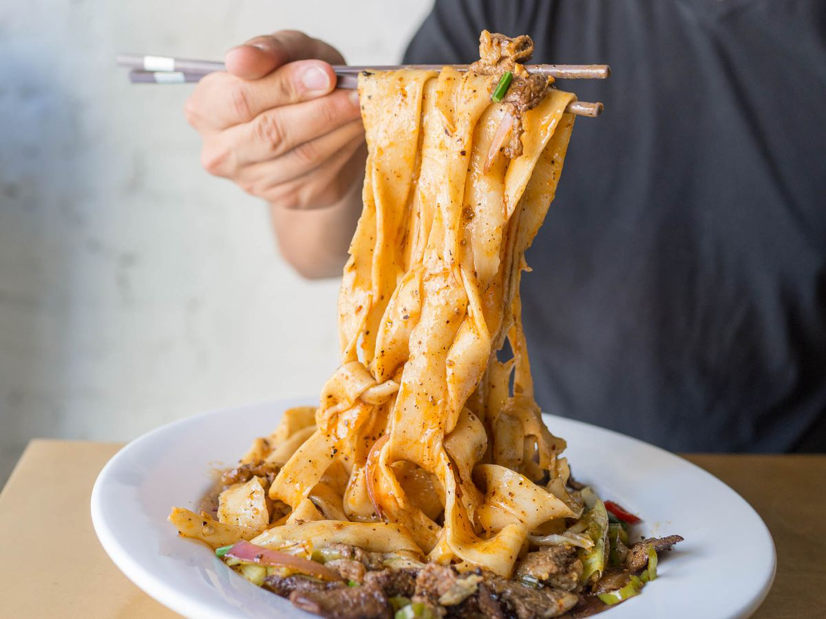 Hand-pulled spicy cumin lamb noodles being lifted with chopsticks