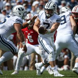 Brigham Young Cougars quarterback Beau Hoge (7) hands the ball off to running back Ula Tolutau (5) during the game against the Wisconsin Badgers at LaVell Edwards Stadium in Provo on Saturday, Sept. 16, 2017.