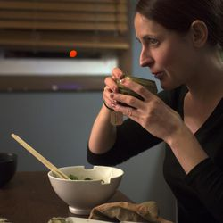 Vegan chef Molly Aubuchon drinks tea while sitting down with her children for a vegan dinner of maki rolls and noodle bowls in her Kent, Ohio, home. Her husband Stefan usually joins the family for dinner but was attempting to fly back from Massachusetts in a winter storm Monday, Feb. 8, 2016.
