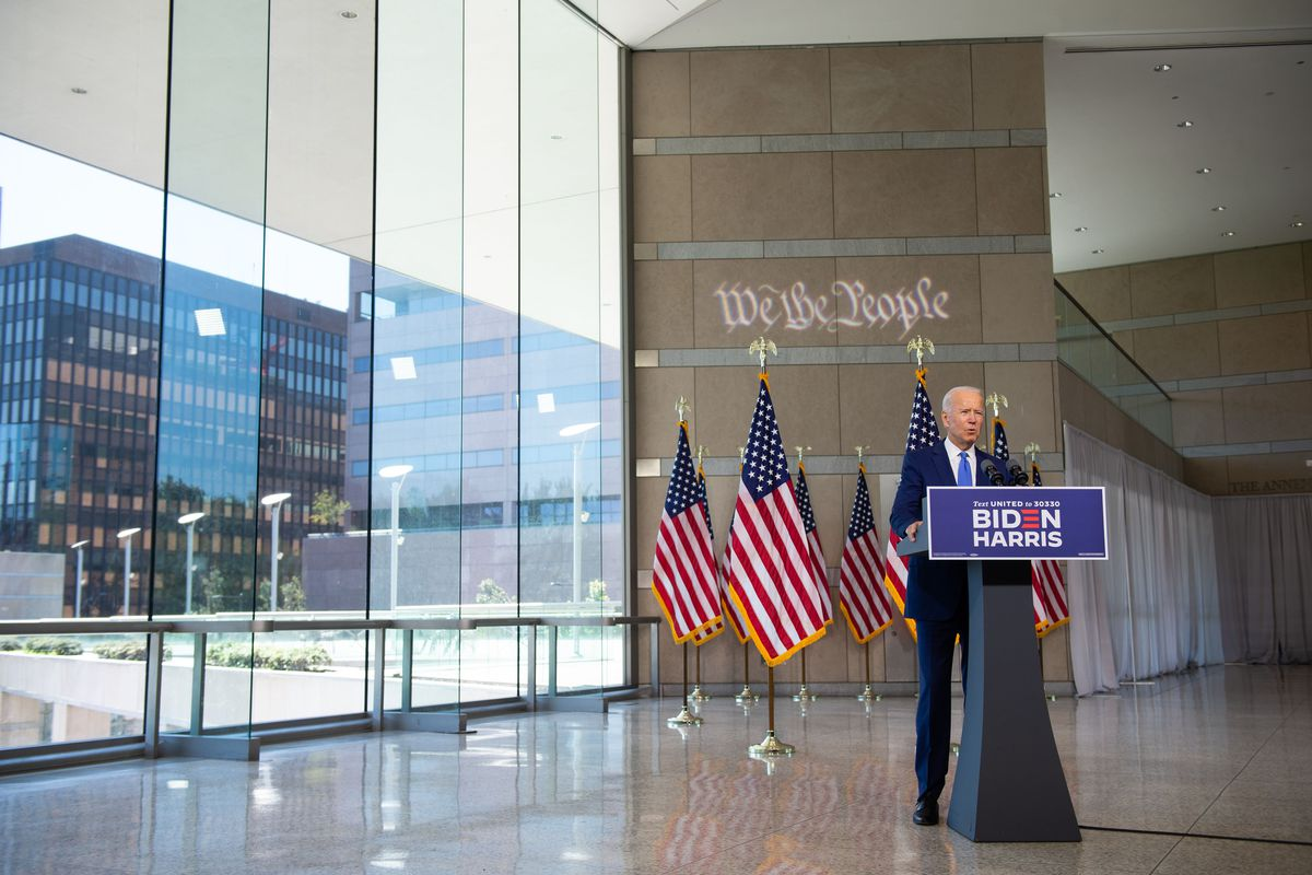 """Biden, in a navy suit and blue tie, stands behind a podium with a sign reading """"Biden Harris."""" To his right are floor to ceiling windows looking out at Philadelphia buildings. Behind him, US flags hang from stands lining the floor in front of a stone wall inscribed with """"We the people."""""""