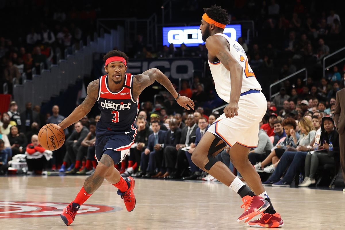 Washington Wizards guard Bradley Beal drives to the basket as New York Knicks center Mitchell Robinson defends in the third quarter at Capital One Arena.