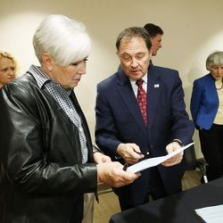 Gov. Gary R. Herbert gives homeless advocate and businesswoman Gail Miller a ceremonial copy after signing two bills — HB436 and HB437 — at the Fourth Street Clinic in Salt Lake City on Friday, March 25, 2016. HB346 will pump $9.25 million into homeless services and shelters, the first of three years of funding that should eventually amount to $27 million. HB347 will provide $15 million to expand Medicaid coverage to the state's poorest of the poor.