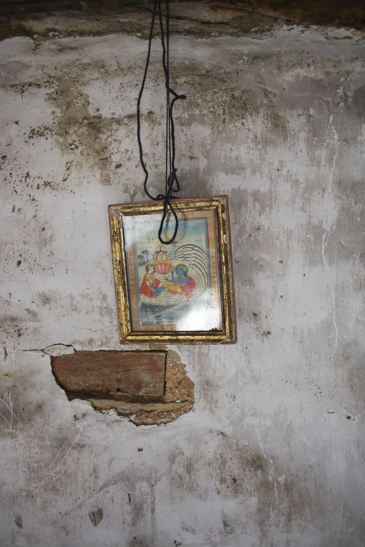 A detail shot of rough plaster, with some of it chipped away and showing the lathe. A picture hangs on the wall.