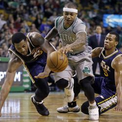 Boston Celtics guard Isaiah Thomas drives through the defense of Utah Jazz forward Derrick Favors, left, and guard Rodney Hood, right, during the second half of an NBA basketball game in Boston, Wednesday, March 4, 2015. The Celtics won 85-84. (AP Photo/Elise Amendola)