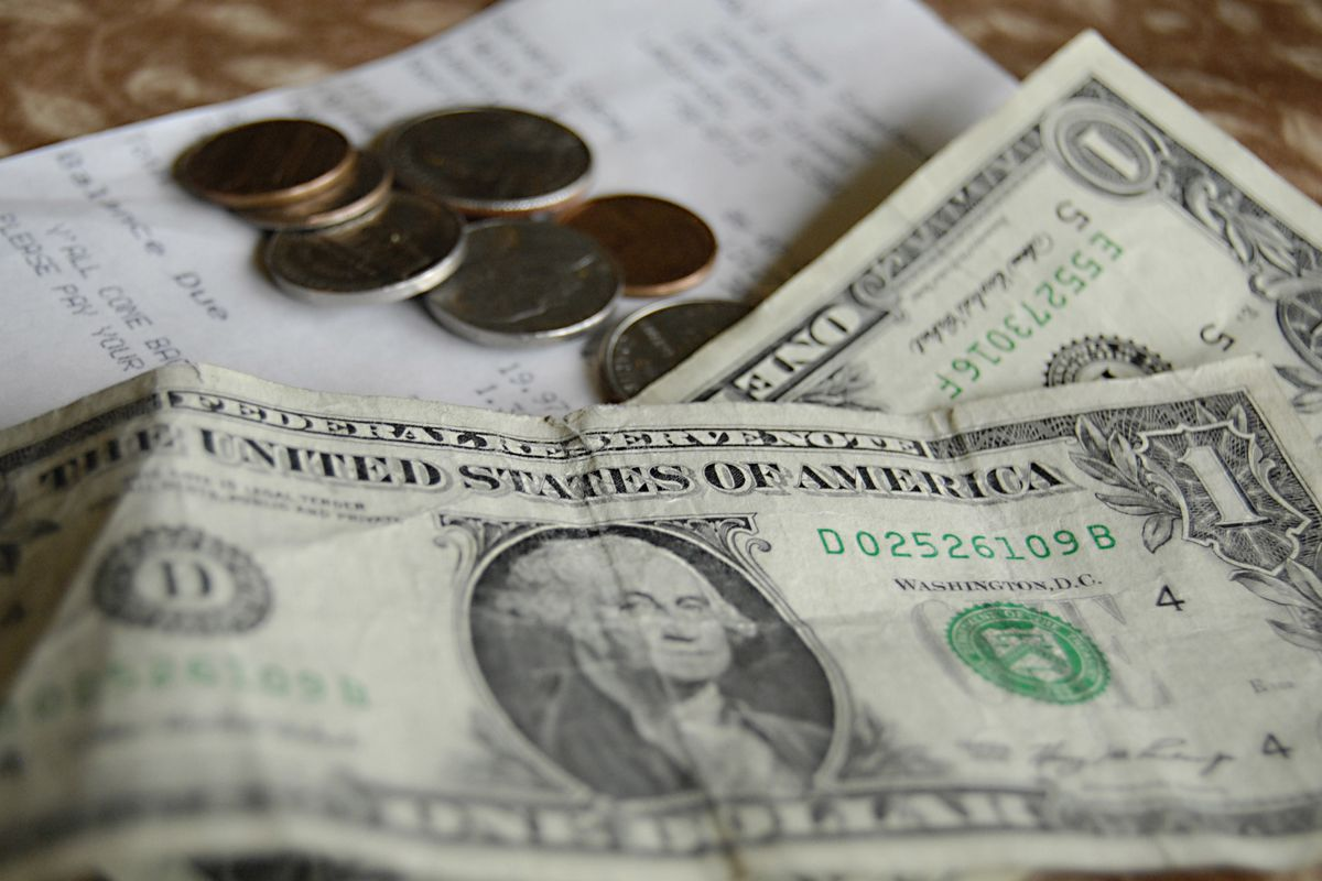 Waiter collecting tip money after check has been paid in local restaurant.