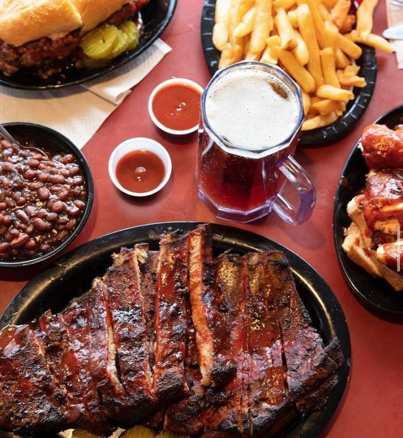 A table spread with a big plate of ribs, a small dish of baked beans, a stein of beer, fries, a burnt ends hoagie, and sauces