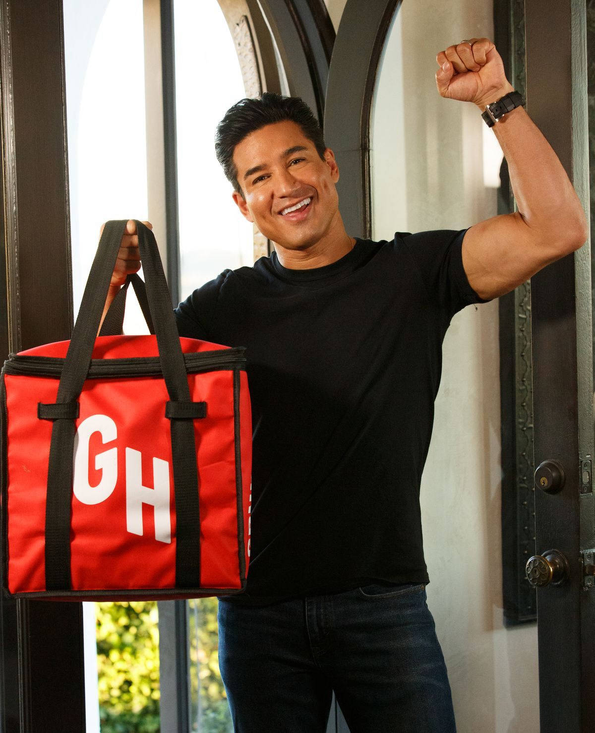 A smiling person flexing his left arm and holding a red insulated bag in the right hand.