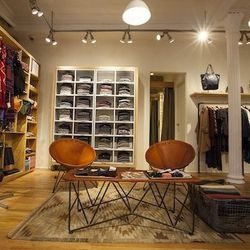 """Men's shirts from the in-house label are folded neatly in compartments along the back wall. The compartments are labeled with style names such as """"collegiate"""" and """"single needle.""""  And, that little basket in the seating area holds cozy, thick blankets."""