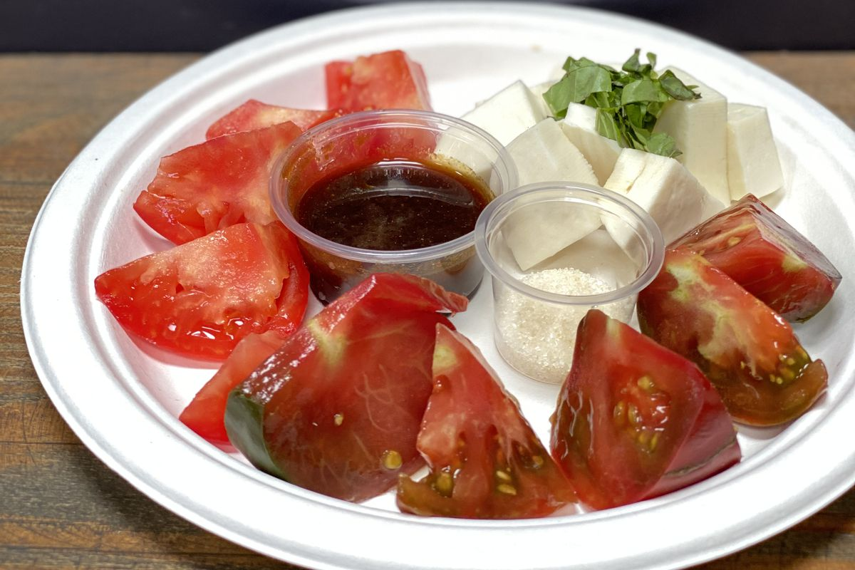 Wedges of juicy red heirloom tomatoes and cubes of mozzarella on a plate, with small tubs of sugar and soy sauce glaze for dipping