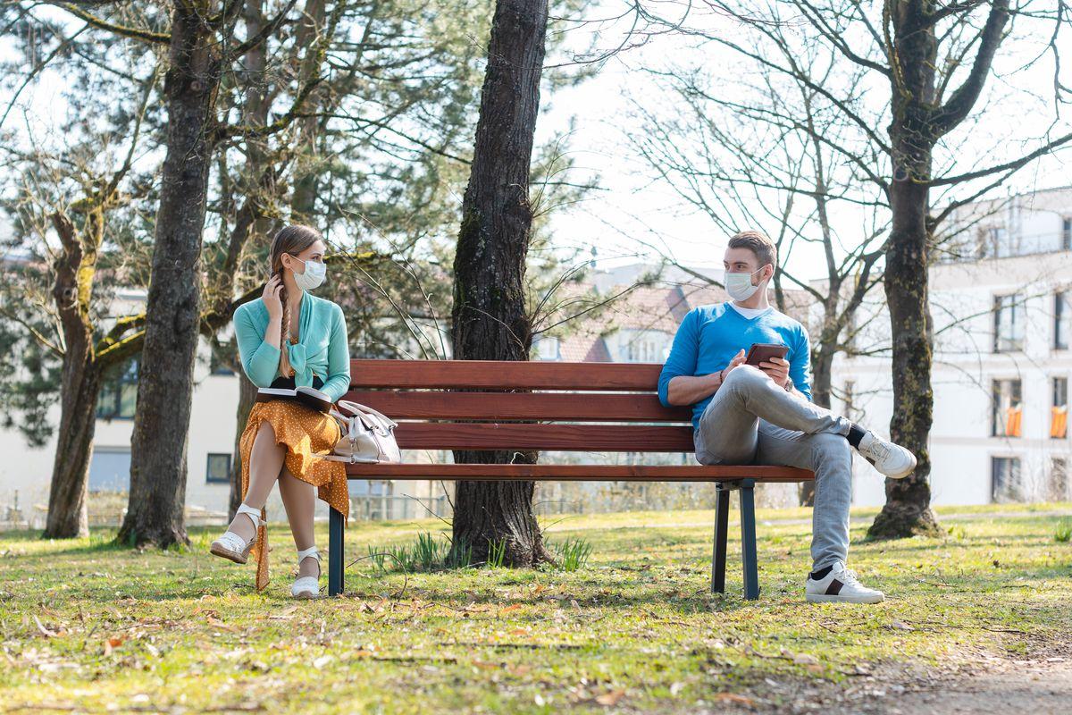 A man and a woman flirt sitting 6 feet apart on a park bench.