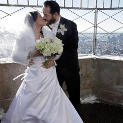 Maria Vasquez and Brendan Goldblatt, from New York, kiss as they pose for photos on the Observation Deck of New York's Empire State Building,  Friday, Feb. 14, 2014.