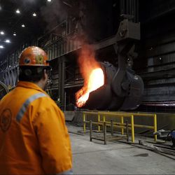 Senior melt operator Randy Feltmeyer watches a giant ladle as it backs away after pouring its contents of red-hot iron into a vessel in the basic oxygen furnace as part of the process of producing steel at the U.S. Steel Granite City Works facility in Granite City, Ill.   AP Photo/Jeff Roberson