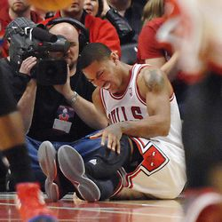 Chicago Bulls point guard Derrick Rose reats after injuring his leg in the fourth quarter of Game 1 in the first round of the NBA basketball playoffs against the Philadelphia 76ers Saturday, April 28, 2012, in Chicago. The Bulls won 103-91.